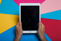 Hands holding an electronic tablet on a multi-color background.