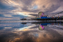 Ferris wheel on a pier at the ocean at dusk.