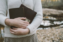 woman holding a Bible and journal to her chest