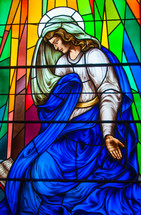 stained glass window of Mary in prayer