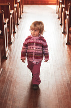 a toddler walking in the aisle of an empty church