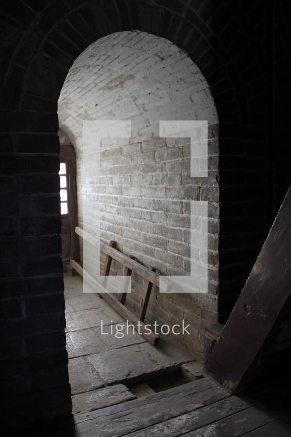 sunlight through a window shining into a cellar hallway