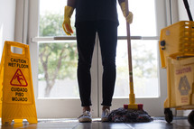 a woman with a mop and mop bucket