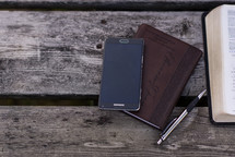 cellphone, journal, pen, and open Bible on a picnic table