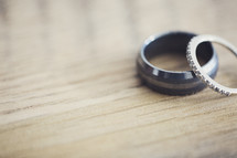 wedding bands on a wooden table top.