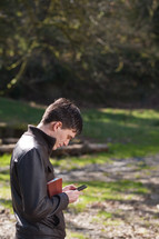 man holding a Bible and texting on his phone outdoors