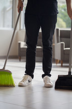 a man with a broom and dust pan in a church lobby