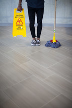 a man holding a mop and wet floor sign