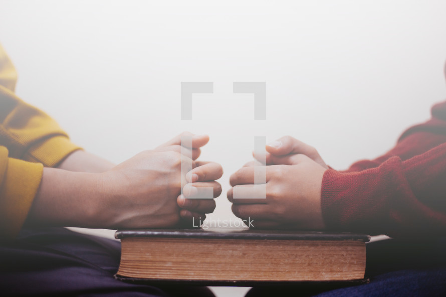 a couple praying together over a Bible