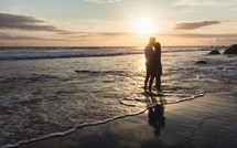a couple embracing on a beach at sunset