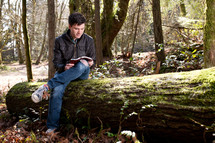 man sitting on a fallen tree reading a Bible in a forest