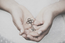 Hands holding a silver key.