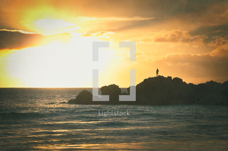 silhouette of a man standing on a shore at sunset