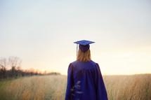 female graduate walking through a field