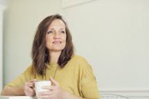 a woman holding a coffee cup and thinking