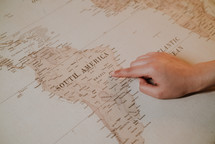 a finger pointing to a map