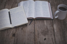 An open Bible and notebook next to a coffee mug