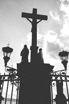 Silhouette of Jesus om the cross with statues in a courtyard.
