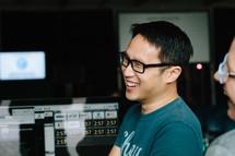 men smiling near control panels