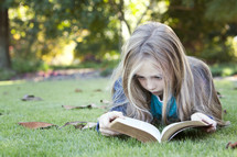 Young girl child reading the Bible outdoors in a park