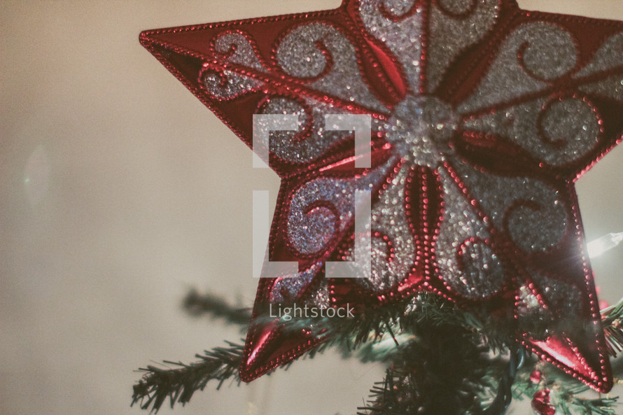 A star ornament at the top of a Christmas tree