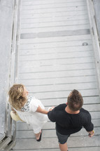 high angle of couple holding hands walking on a boardwalk.