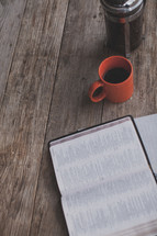 An open Bible, notebook, coffee mug and french press