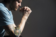 a man with a sleeve tattoo praying.