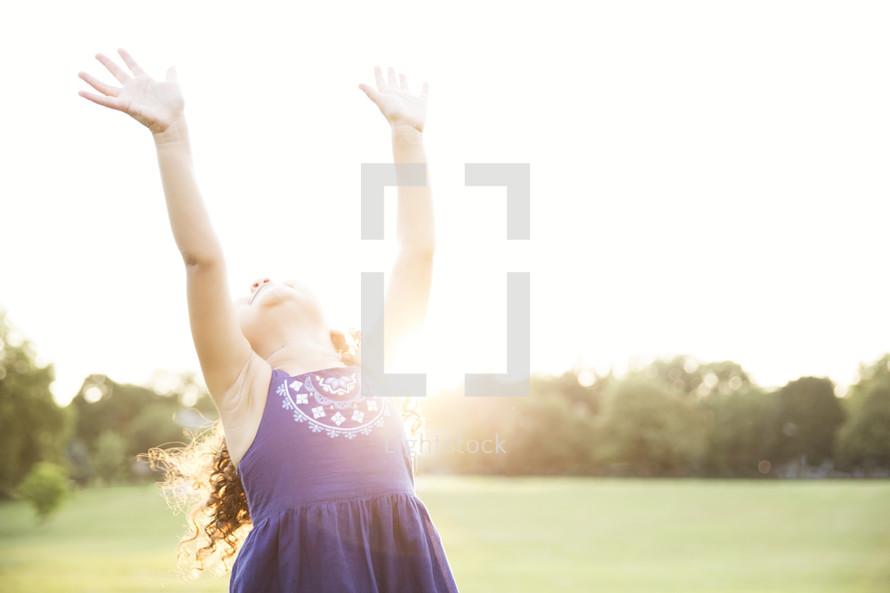 toddler girl with joyful raised hands