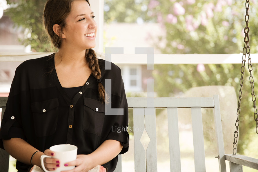 woman on a porch swing with a Bible and coffee mug