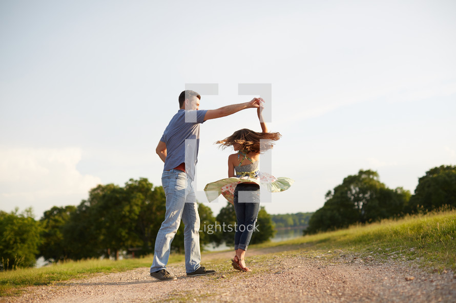 a father dancing with his daughter on a dirt road