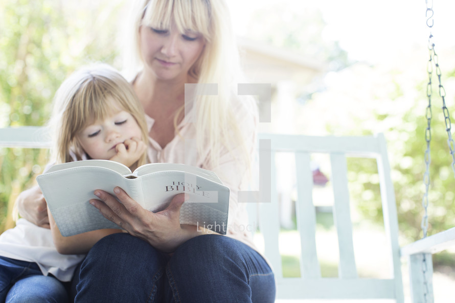 mother reading the Bible with her daughter.