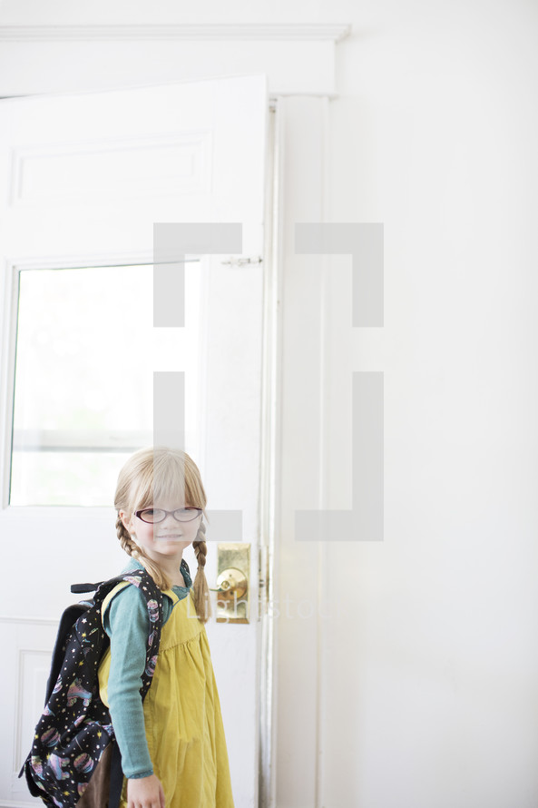 girl child with a backpack opening a door