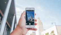 taking a picture of a skyscraper in a city with an iPhone
