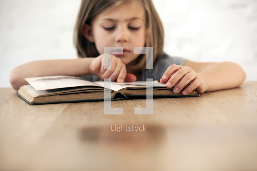 girl reading a children's Bible