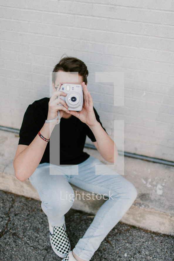 a young man holding a polaroid camera