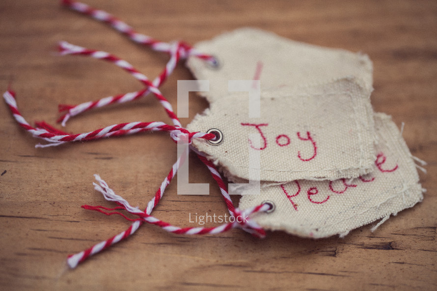 "A stack of Christmas gift tags, the top one reading ""Joy"" on a wood grain background."
