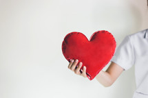 a healthcare worker holding a heart