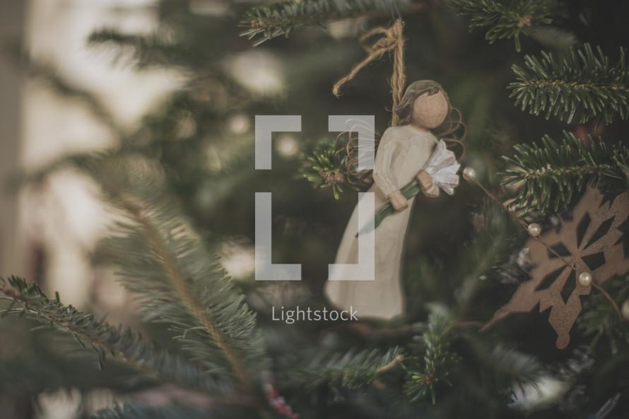 An angel Christmas ornament on a Christmas tree