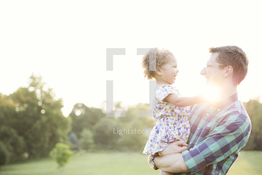 a father holding his toddler daughter outdoors