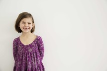 portrait of smiling young girl against white wall.