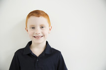 A smiling red haired boy.