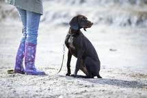 a woman in rain boots and her dog