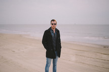 A young man in a coat standing on a beach.