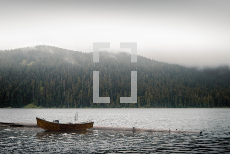 A small boat on a lake surrounded by trees and mountains.