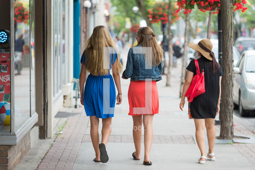 Women walking on a sidewalk in a shopping center.