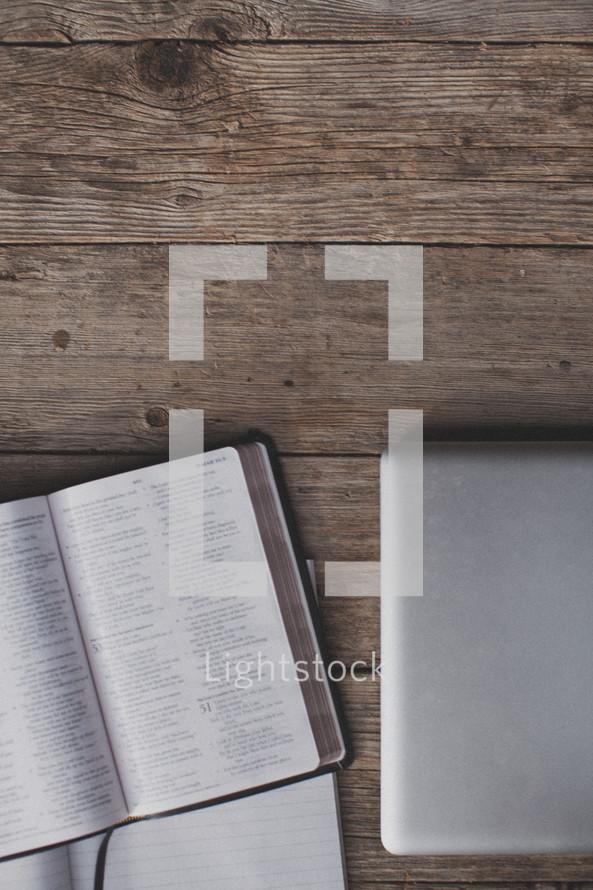 An open Bible, notebook and laptop