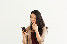 a woman reacting to something she read on her cellphone screen