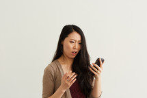 a woman reacting to something he read on his cellphone screen