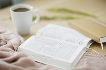 open Bible, coffee, mug, and journal on a table